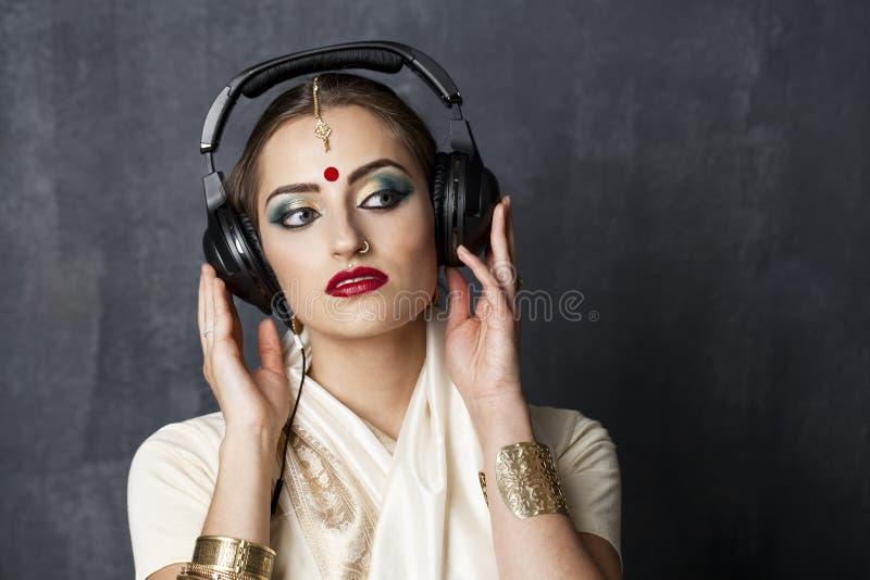 Härlig indisk kvinna som lyssnar till musik på hörlurar fotografering för bildbyråer