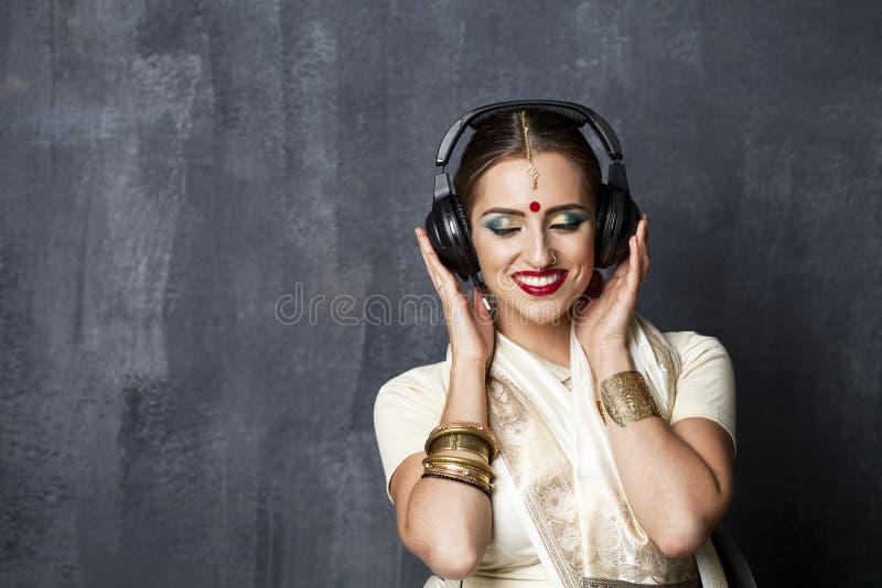 Härlig indisk kvinna som lyssnar till musik på hörlurar royaltyfria bilder