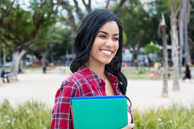 Härlig infödd latin - amerikansk kvinnlig student utomhus på campu royaltyfri foto