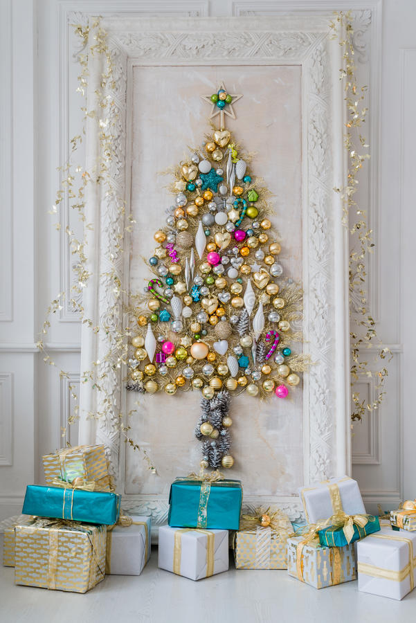 Härlig inre vardagsrum som dekoreras för jul Stor spegelram med ett träd som göras av bollar och leksaker royaltyfri foto