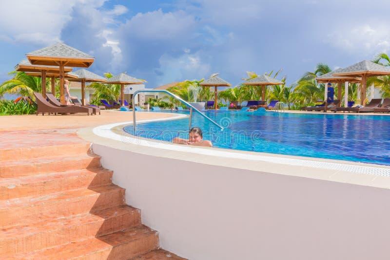 Härlig inviterande sikt av den bekväma hemtrevliga simbassängen med le simning och att tycka om för liten flicka avslappnande hen royaltyfria foton
