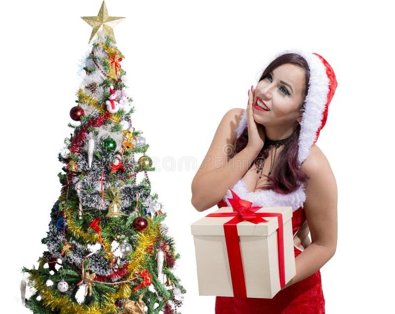 Härlig jul som ler den egyptiska flickan i den Santa Claus dräkten med gåvaasken bredvid julträd arkivbilder
