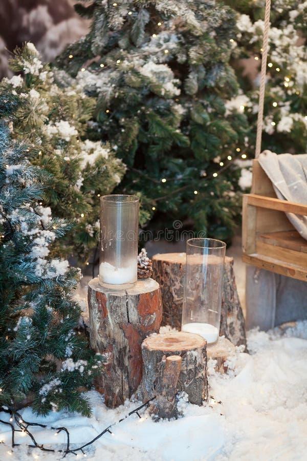 Härlig julinredesign Närbild av den dekorerade snö-täckte julgranen med stubbar, stearinljus i exponeringsglas arkivbilder