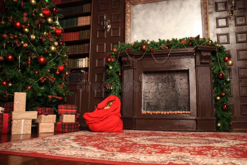 Härlig julvardagsrum med den dekorerade julgranen, gåvor och spisen med glöda tänder på natten arkivfoto