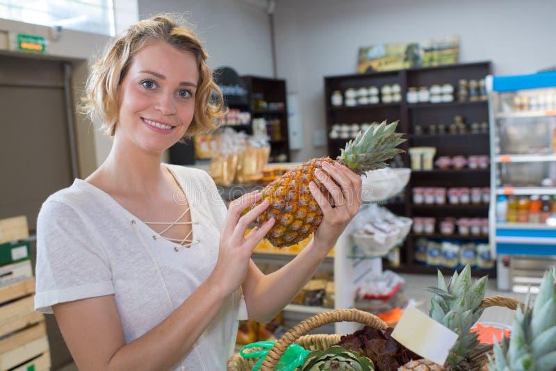 Härlig köpandeananas för ung kvinna i fruktmarknad arkivbild