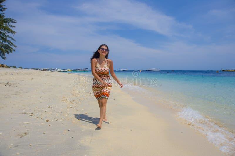 Härlig kinesisk asiatisk flicka i sommarklänning som går på strandsand med fantastisk härlig färg för turkoshavsvatten som tycker arkivfoto