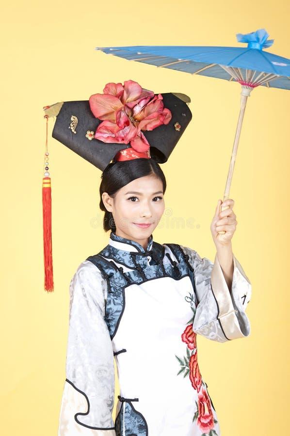 Download Härlig Kinesisk Kvinna Som Bär Den Traditionella Dräkten Mot Gul Bakgrund Arkivfoto - Bild av dräkt, gulligt: 78731328