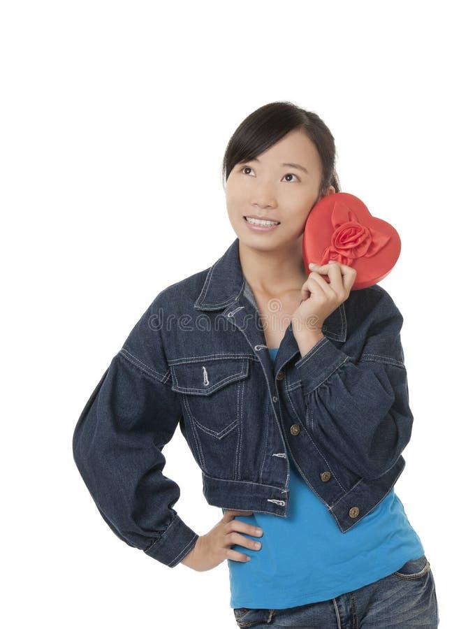 Härlig kinesisk kvinna som rymmer en röd hjärta royaltyfria foton