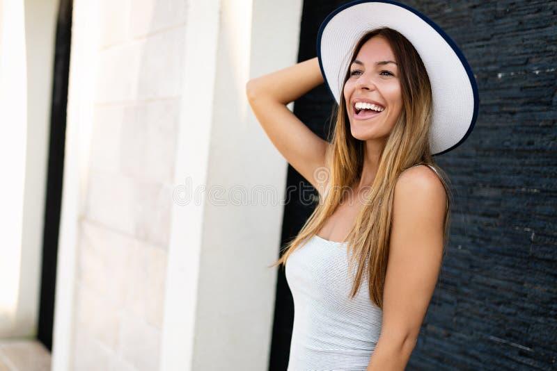 Härlig klänning för ung kvinna för brunett bärande och hatt, le som är utomhus- royaltyfria bilder