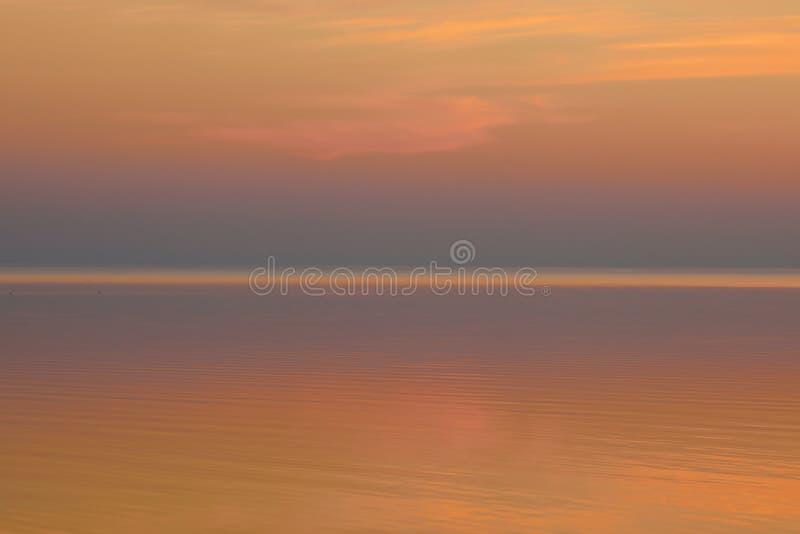 Härlig klar bakgrundssolnedgångfärg över sjön arkivbilder