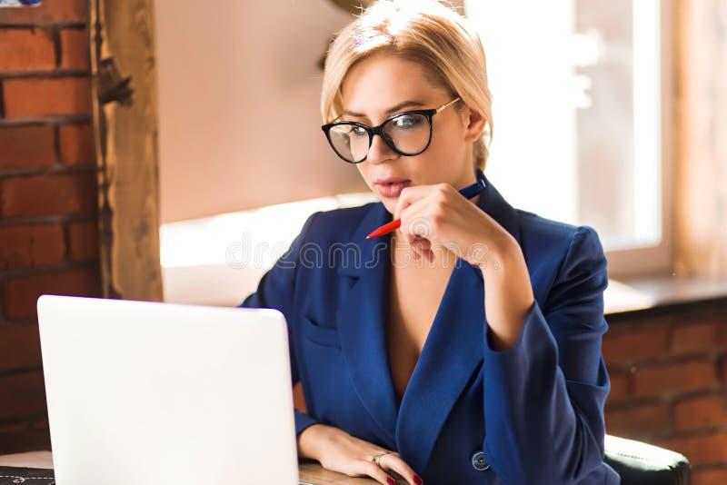 Härlig klyftig affärskvinna som sitter på tabellen på arbetsstationen med bärbara datorn arkivfoto
