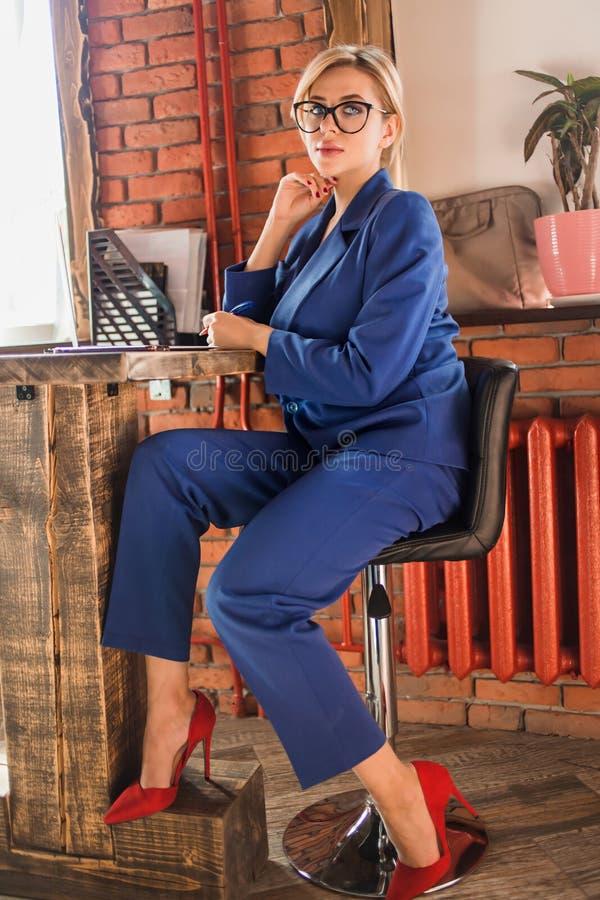 Härlig klyftig affärskvinna som sitter på tabellen på arbetsstationen med bärbara datorn royaltyfria foton