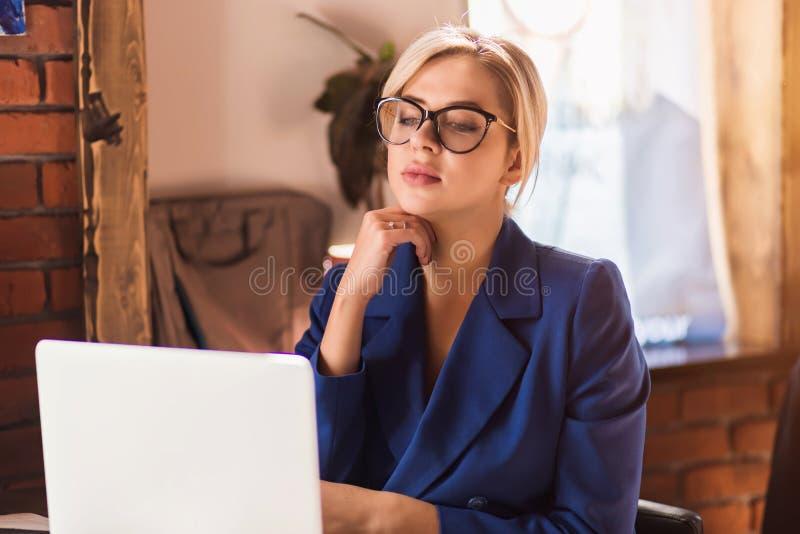Härlig klyftig affärskvinna som sitter på tabellen på arbetsstationen med bärbara datorn arkivbild