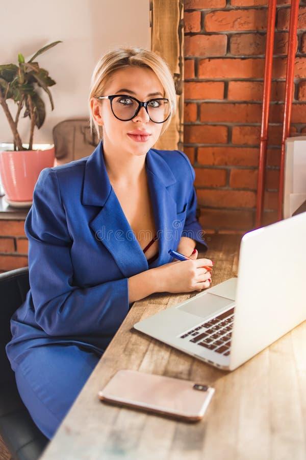 H?rlig klyftig aff?rskvinna som sitter p? tabellen p? arbetsstationen med b?rbara datorn arkivfoto