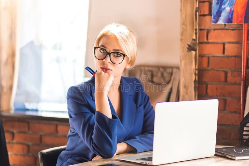 Härlig klyftig affärskvinna som sitter på tabellen på arbetsstationen med bärbara datorn royaltyfri fotografi