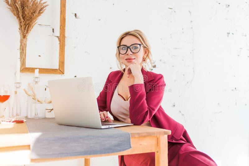 Härlig klyftig affärskvinna som sitter på tabellen på arbetsstationen med bärbara datorn royaltyfri foto