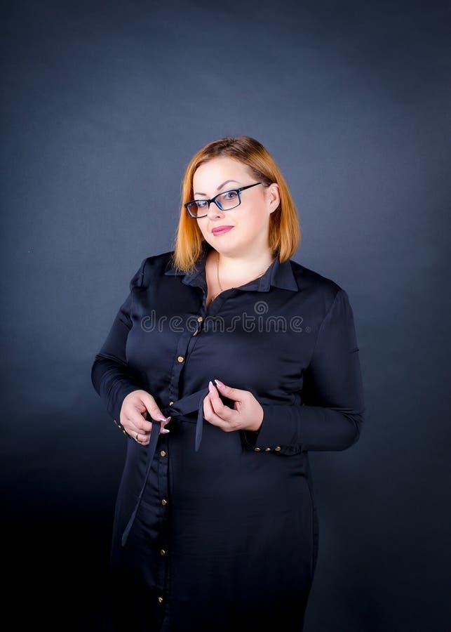 Härlig knubbig flicka i en svart klänning på en mörk bakgrund arkivbild