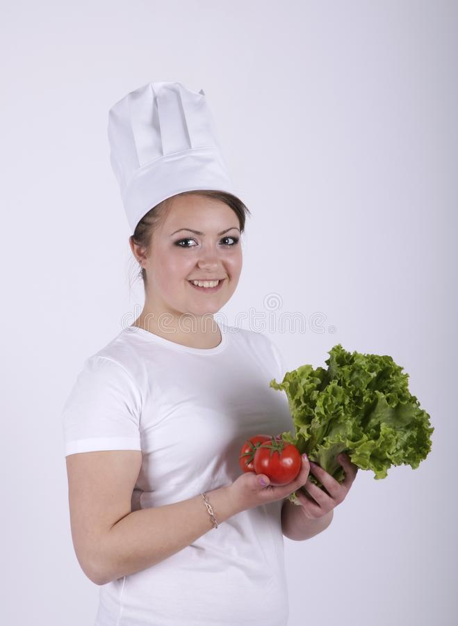 Härlig kock som gör ny sallad royaltyfri fotografi