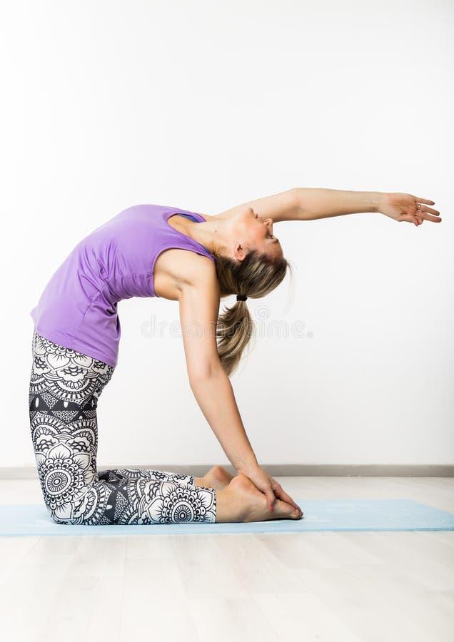 Härlig konditionkvinna som gör yogaövningar på en ljus bakgrund arkivbild