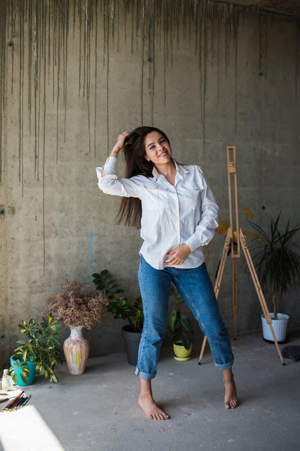 Härlig konstnär för ung dam i den vita skjortan som barfota dansar i hennes bohemiska konstnärliga studiovind arkivfoto