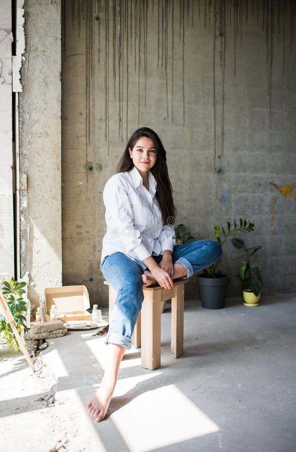 Härlig konstnär för ung dam i den vita skjortan som barfota sitter i hennes bohemiska konstnärliga studiovind royaltyfria bilder