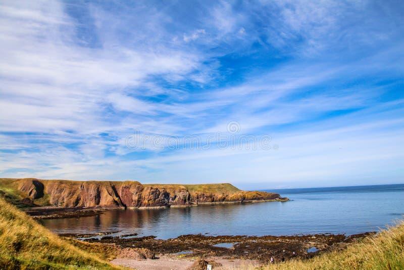 Härlig kulle mot blå himmel som täckas med cirrusmolnmoln och det blåa havet fotografering för bildbyråer