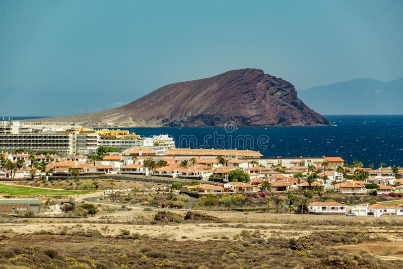 Härlig kust- sikt av det Montana Roja Red Mountain berget i Tenerife Del av den Gran Canaria ön i en ljus ogenomskinlighet i arkivfoton