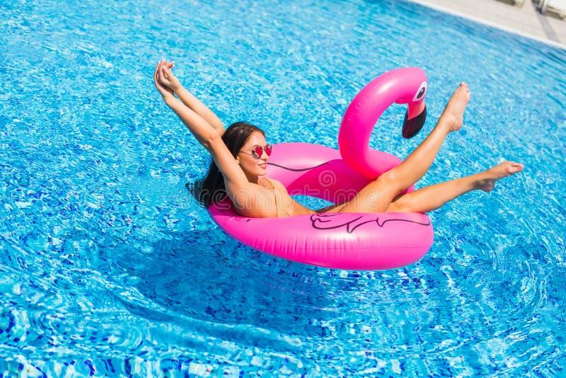 Härlig kvinna, bärande baddräkt som ligger på en rosa flamingoluftmadrass i en pöl av blått vatten, sommar arkivbild