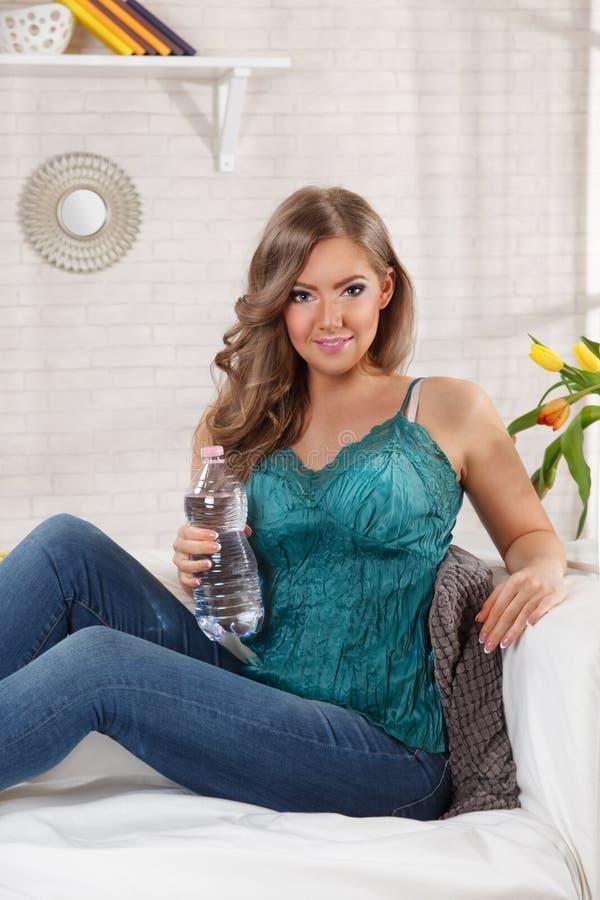 härlig kvinna för flaskholdingvatten arkivbild