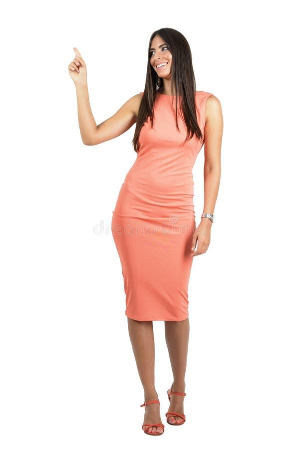 Härlig kvinna för gladlynt glamour i aftonklänning som pekar upp med fingret arkivfoto