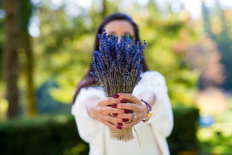 Härlig kvinna för mode som rymmer en lavanderbukett arkivbild