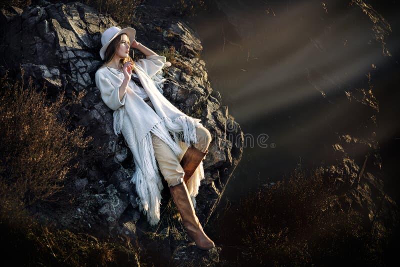 Härlig kvinna för modemodell som poserar i berg på solnedgången royaltyfri fotografi
