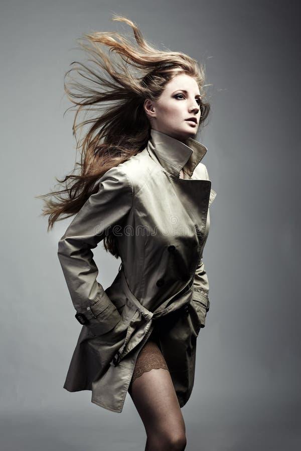 härlig kvinna för modeståenderaincoat fotografering för bildbyråer