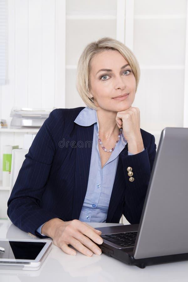Härlig kvinna för mogen affär i hennes kontor. royaltyfri foto