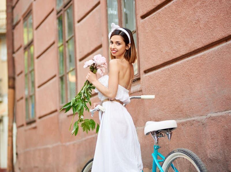 Härlig kvinna för närbild med pioner i händer nära den retro cykeln royaltyfri foto