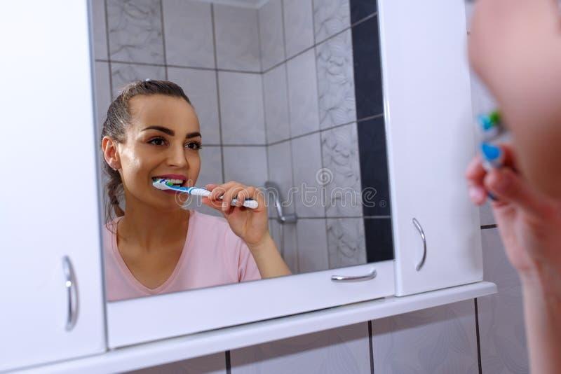 Härlig kvinna för sunda tänder som borstar hennes tänder i badrum royaltyfri bild