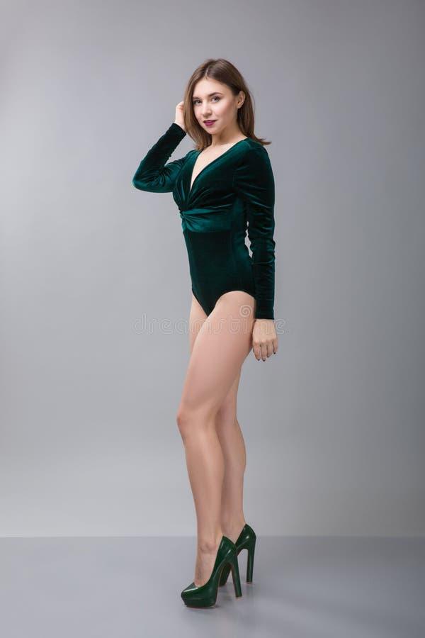 Härlig kvinna för svart hår i mörker - långa muffar för grön bodysuitwuth som poserar på kameran mot grå bakgrund fotografering för bildbyråer