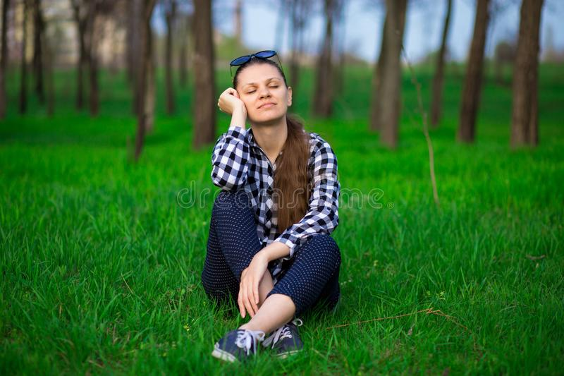 Härlig kvinna för ungt brunettanbud med stängda ögon som sitter på att koppla av för gräs fotografering för bildbyråer