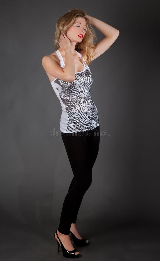 Härlig kvinna i ärmlös tröja och damasker royaltyfria bilder