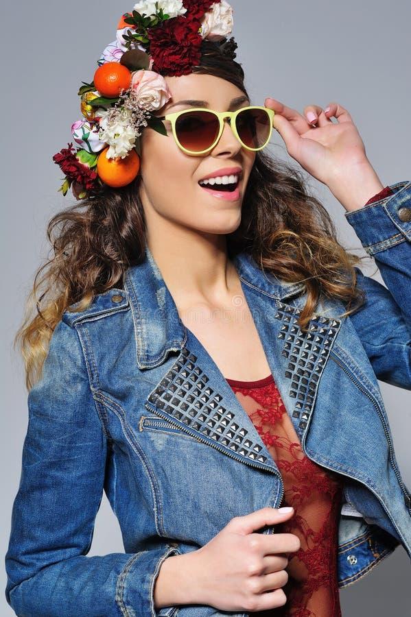 Härlig kvinna i bärande solglasögon för blommakrona arkivbild
