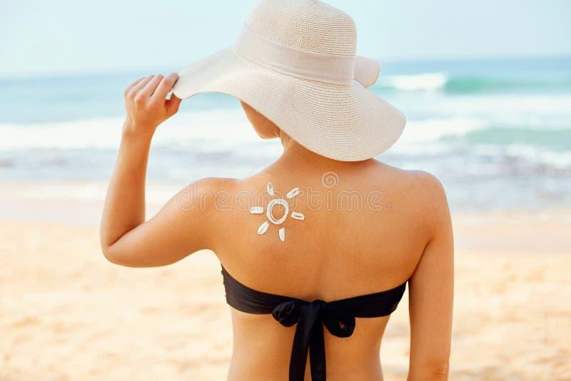 Härlig kvinna i bikinin som applicerar solkräm på brunbränd skuldra Kvinna som s?tter sol- kr?m p? skuldra n?ra p?len Hud och kro royaltyfria bilder
