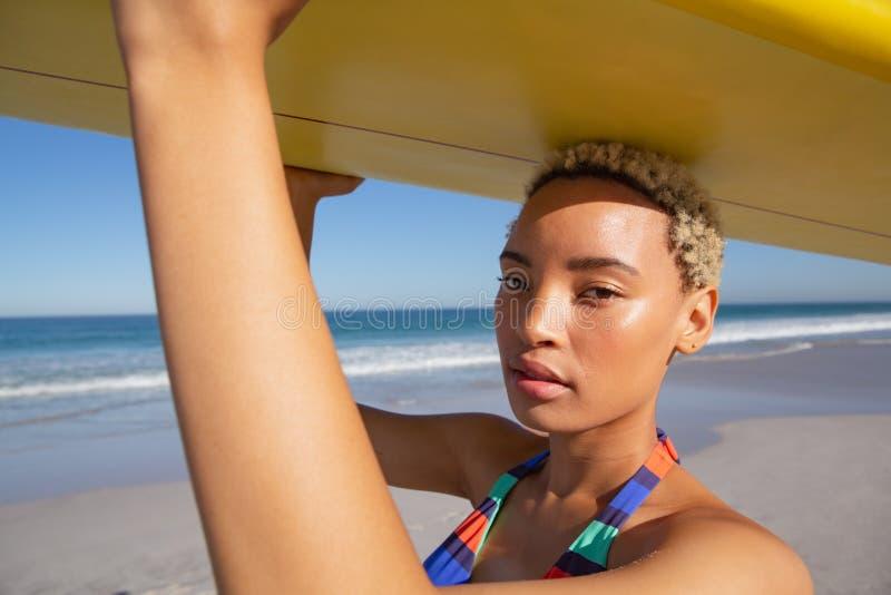 Härlig kvinna i bikinin som bär surfingbrädan på hennes huvud på stranden i solskenet royaltyfri fotografi
