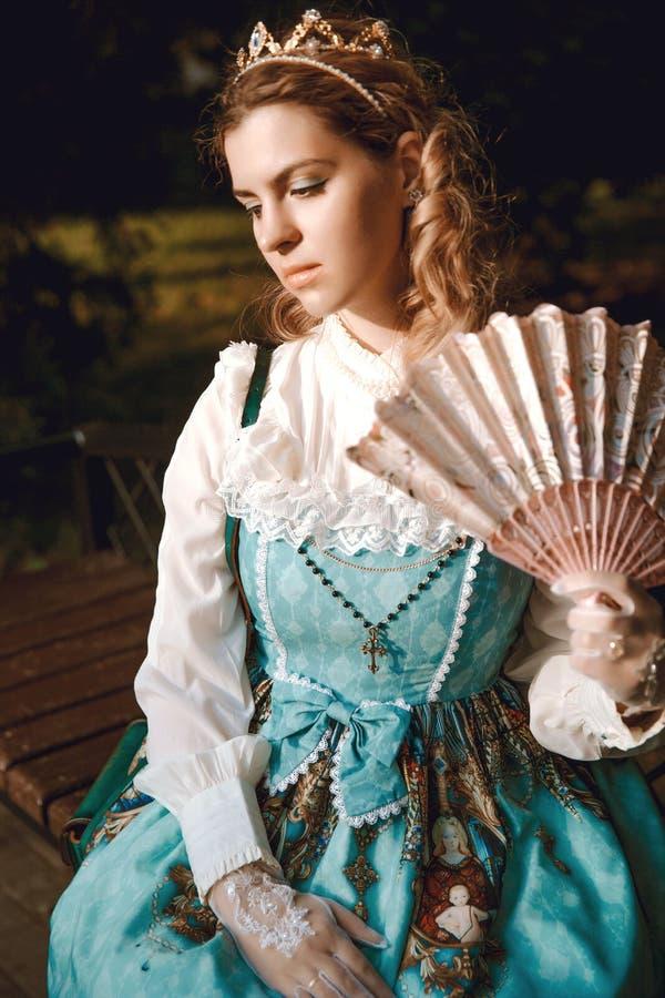 Härlig kvinna i blå klänning för tappning med fanen i kronadiadem Viktoriansk dam elegantt royaltyfri fotografi