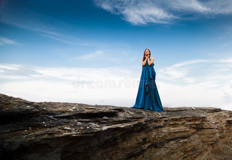 Härlig kvinna i blå lång klänning royaltyfria bilder