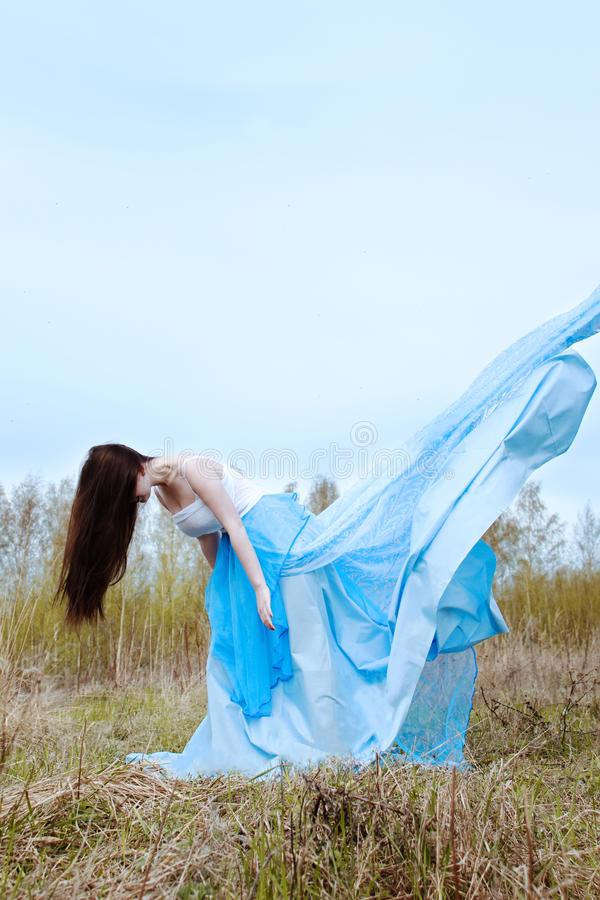 Härlig kvinna i blå lång klänning med flygtyg royaltyfria foton