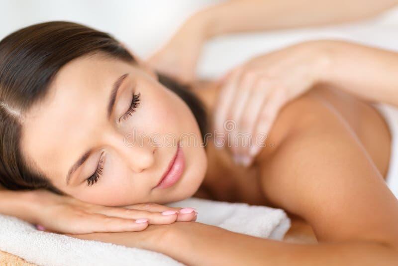 Härlig kvinna i brunnsortsalongen som får massage arkivfoto