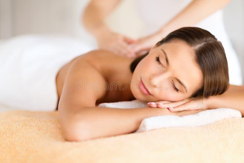 Härlig kvinna i brunnsortsalongen som får massage royaltyfria foton