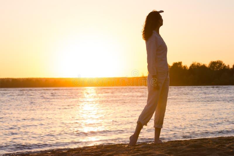 Härlig kvinna i den naturliga vita skjortan som ser till den guld- solen royaltyfri foto