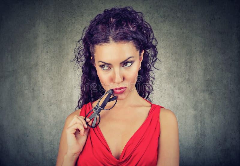Härlig kvinna i den röda klänningen som rymmer glasögon och ser bort i beslut på grå bakgrund fotografering för bildbyråer