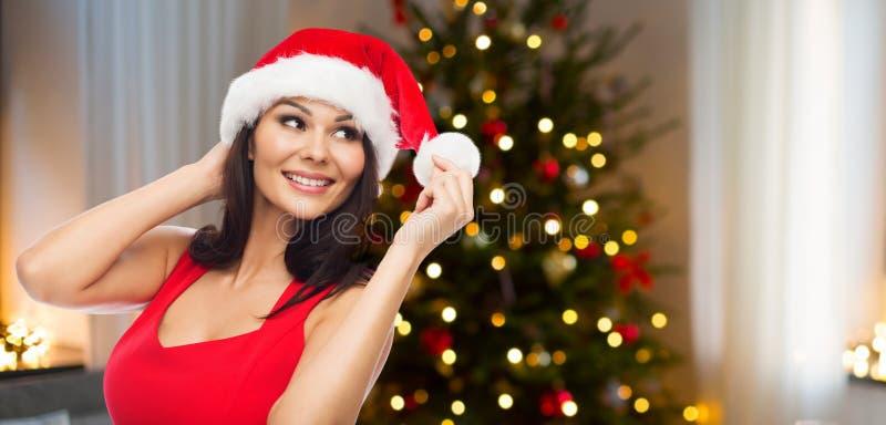 Härlig kvinna i den santa hatten över julträd arkivfoton